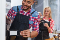 Barista making coffee shop staff man and woman happy smile. Barista making coffee shop staff men and women happy smile working at bar counter mix race Royalty Free Stock Images