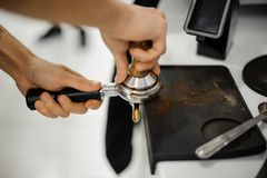 Barista making a coffee tablet with help of temper Royalty Free Stock Image