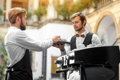 Barista making coffee with waiter Royalty Free Stock Images