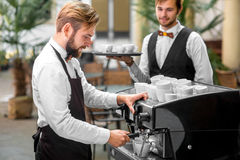 Barista making coffee with waiter Royalty Free Stock Photo