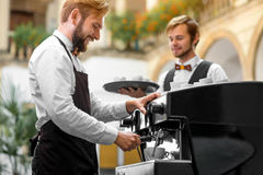 Barista making coffee with waiter Stock Images