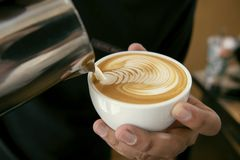Barista making latte or Cappuccino art with frothy foam, coffee royalty free stock photo