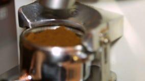 Barista mala och fördelande jordkaffe från molar till portafilter arkivfilmer