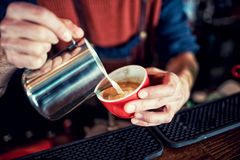 Barista man creating latte art on long coffee with milk. Latte art in coffee mug. Barman pouring fresh coffee. Barista creating latte art on long coffee with Royalty Free Stock Images