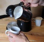 Barista man is making cappuccino. Pours milk closeup Stock Photo