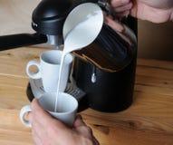 Barista man is making cappuccino. Pours milk closeup Stock Photos