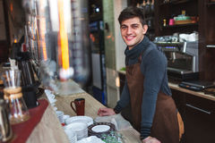 Barista man portrait behind the bar in cafe. Happy barista man portrait behind the bar in cafe Royalty Free Stock Image