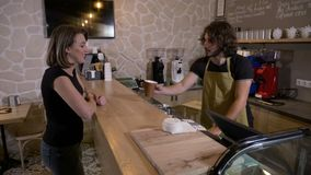 Barista man serving a female costumer with a to go drink who pays for it with crypto currency bitcoin from smartphone mobile app -. Young barista man serving a stock video