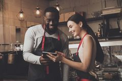 Barista man and woman looking at a tablet stock images