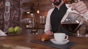 Barista-Mann hält einen Werfer frischen gebrauten Kaffee und gießt herein einen leeren Cup stock video