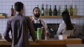 Barista masculino que comunica con el cliente en el café almacen de metraje de vídeo