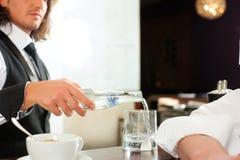 Barista med beställare i hans cafe eller coffeeshop Arkivfoton