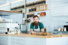 Barista med skägg- och mustaschanseende i coffee shop Royaltyfria Bilder