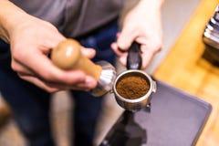 Barista met stamper en zuiger, portafilter voor een molen die espresso maken stock afbeelding