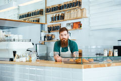 Barista mit dem Bart und Schnurrbart, die in der Kaffeestube stehen Lizenzfreie Stockbilder