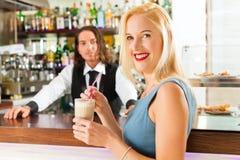 Barista mit Kunden in seinem Café oder in coffeeshop Stockbild