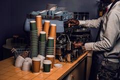 Barista n biały fartuch i koszula robimy kawie na kawowej maszynie w sklepie z kawą obraz stock