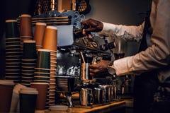 Barista n biały fartuch i koszula robimy kawie na kawowej maszynie w sklepie z kawą zdjęcie royalty free