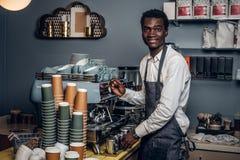 Barista n gör den vita skjortan och förklädet kaffe på kaffemaskinen i en coffee shop royaltyfri bild