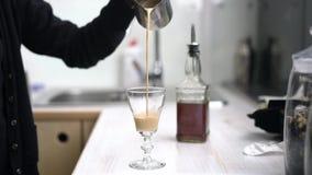 Barista nalewa kawę z mlekiem w szkło zdjęcie wideo