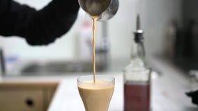 Barista nalewa kawę z mlekiem w szkło zbiory wideo
