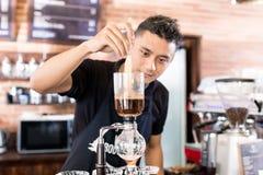 Barista narządzania kapinosa kawa w Azjatyckim sklep z kawą Obrazy Stock