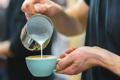 Barista nel bar che prepara cappuccino adeguato che versa latte schiumato nella tazza di caffè, facente arte del latte, modello Fotografia Stock