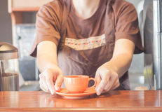 Barista offering mini orange cup of coffee Royalty Free Stock Image