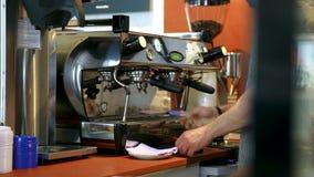 Barista p? den yrkesm?ssiga kaffemaskinen i coffee shop konst Barista tv?ttar och torkar espressomaskinen, innan han g?r koppen arkivfilmer