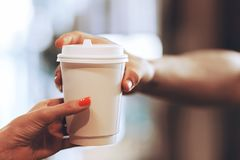 Barista passes coffee to a visitor in a popular coffee shop, hands and a glass of coffee are shot close-up. royalty free stock image