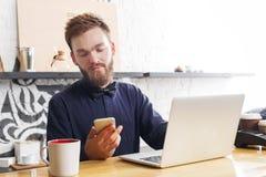 Barista pensieroso che lavora al computer portatile al contatore della barra Immagine Stock