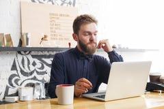 Barista pensieroso che lavora al computer portatile al contatore della barra Immagine Stock Libera da Diritti