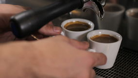 Barista picks up two cups of fresh made espresso. Close up stock footage