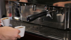 Barista picks up two cups of fresh made espresso. Medium shot stock video footage