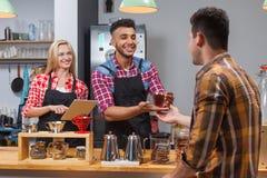 Barista porci klient daje szklanemu herbacianemu sklep z kawą baru kontuarowi Zdjęcia Royalty Free
