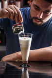 Barista is pouring coffee in milk Royalty Free Stock Photos