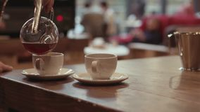 Barista is pouring coffee from a vacuum coffee maker into two white cups placed on the soft oak table, in a cafe. Cafe stock video footage