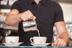 Barista. Pouring Froth Art. Indoor shoot Royalty Free Stock Image