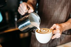 Barista pouring latte foam over coffee, espresso and creating a perfect latte art royalty free stock photos