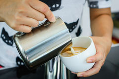 Barista pouring milk in capuccino coffee Royalty Free Stock Photo