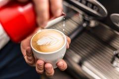 Barista pouring milk. Closeup of barista pouring milk into art cappuccino Royalty Free Stock Photography