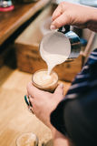 Barista pouring milk into coffee Royalty Free Stock Photos