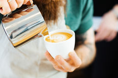 Barista pouring milk into cup of coffee Stock Photo