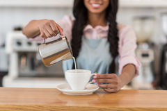 Barista pouring milk into cup of coffee Stock Photography