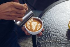 Barista pouring milk foam for making coffee latte art with pattern the leaves in a cup stock photos
