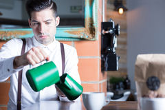 Barista pouring milk from one pitcher to another Stock Photo