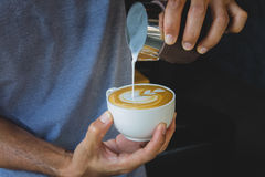 Barista pouring milk from pitcher to a cup of coffee making latte art stock image