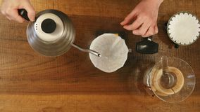 Barista pouring water on coffee ground with filter stock footage