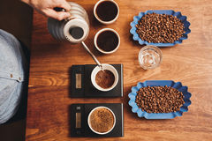 Barista pouring water into cup of ground coffee on scale. Overhead shot of a professional barista pouring hot water from a stainless steel kettle into a cup with Stock Photos