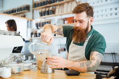 Barista pouring water in glass Royalty Free Stock Images